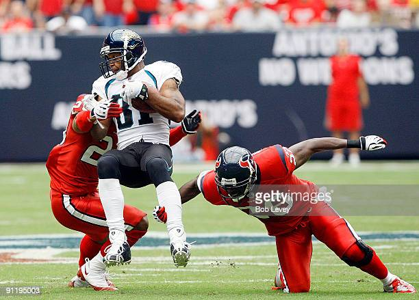 Wide receiver Torry Holt of the Jacksonville Jaguars is tripped up by free safety Eugene Wilson and cornerback Dunta Robinson of the Houston Texans...