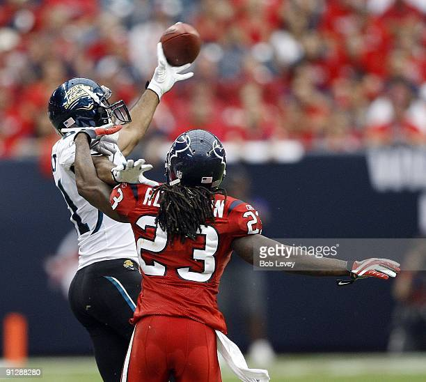 Wide receiver Torry Holt of the Jacksonville Jaguars makes an one handed attempt to gather in this pass as cornerback Dunta Robinson of the Houston...
