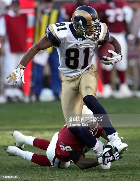 Wide receiver Torry Holt of the St Louis Rams carries the ball as cornerback Duane Starks of the Arizona Cardinals trips him up on December 19 2004...