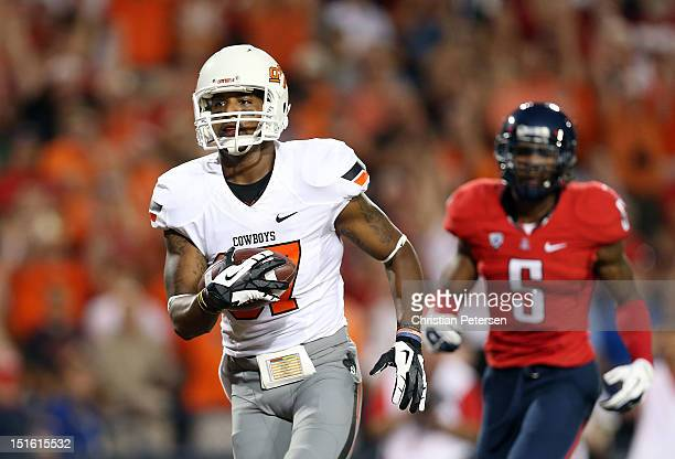 Wide receiver Tracy Moore of the Oklahoma State Cowboys scores a 30 yard touchdown reception past cornerback Shaquille Richardson of the Arizona...