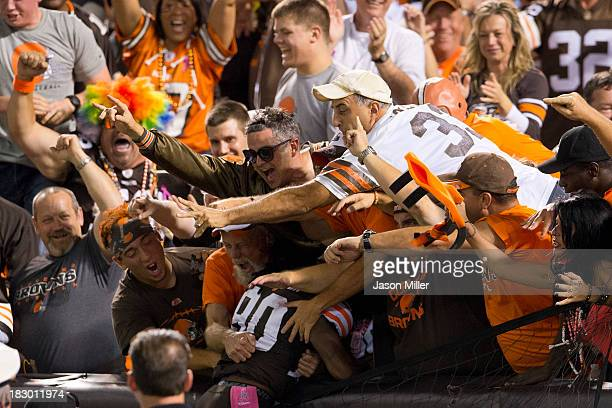 Wide receiver Travis Benjamin of the Cleveland Browns celebrates in the Dog Pound after returning a punt return for a touchdown during the first half...