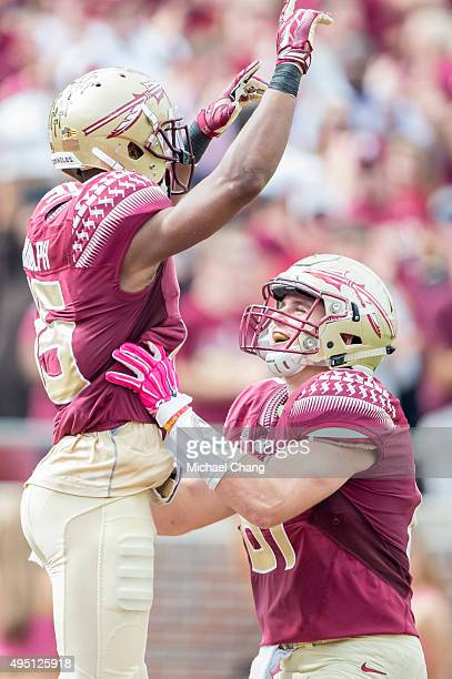 Wide receiver Travis Rudolph celebrates with tight end Ryan Izzo of the Florida State Seminoles after scoring a touchdown during their game against...