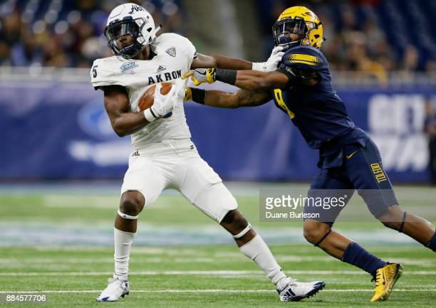 Wide receiver Tra'Von Chapman of the Akron Zips stiffarms cornerback Josh Teachey of the Toledo Rockets while carrying the ball during the first half...