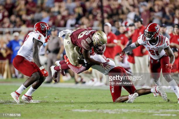 Wide Receiver Tre'Shaun Harrison of the Florida State Seminoles is tackled by Cornerback Teshaun Smith of the North Carolina State Wolfpack during...