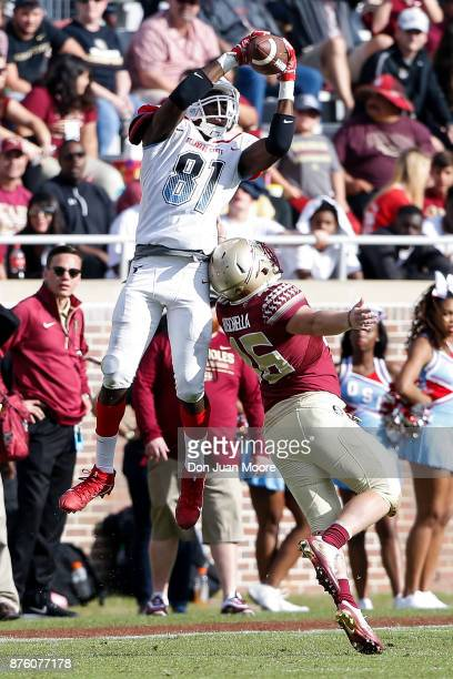 Wide Receiver Trey Gross of the Delaware State Hornets makes a catch over Defensive Back John Moschella III of the Florida State Seminoles during the...