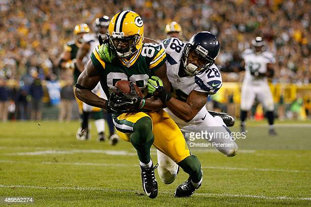 Wide receiver Ty Montgomery of the Green Bay Packers runs with the football after a reception past defensive back Marcus Burley of the Seattle...
