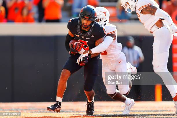 Wide receiver Tylan Wallace of the Oklahoma State Cowboys catches an 11yard touchdown pass against defensive back Josh Thompson of the Texas...