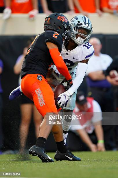 Wide receiver Tylan Wallace of the Oklahoma State Cowboys holds onto a 12yard catch against defensive back AJ Parker of the Kansas State Wildcats at...
