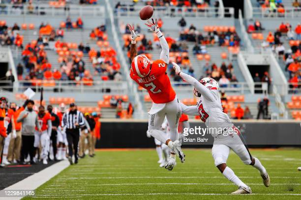 Wide receiver Tylan Wallace of the Oklahoma State Cowboys makes a 40-yard catch against defensive back DaMarcus Fields of the Texas Tech Red Raiders...