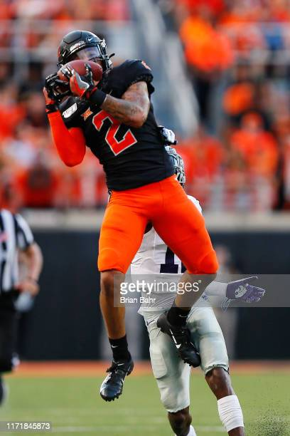 Wide receiver Tylan Wallace of the Oklahoma State Cowboys pulls down a 33yard catch against defensive back AJ Parker of the Kansas State Cowboys in...