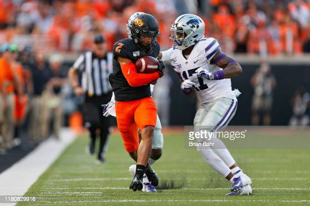 Wide receiver Tylan Wallace of the Oklahoma State Cowboys pulls down a 33yard catch against defensive back AJ Parker as defensive back Jonathan...