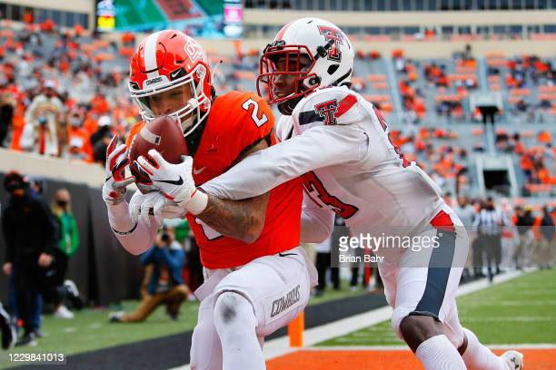 Wide receiver Tylan Wallace of the Oklahoma State Cowboys reaches up for a 27-yard touchdown catch against defensive back DaMarcus Fields of the...