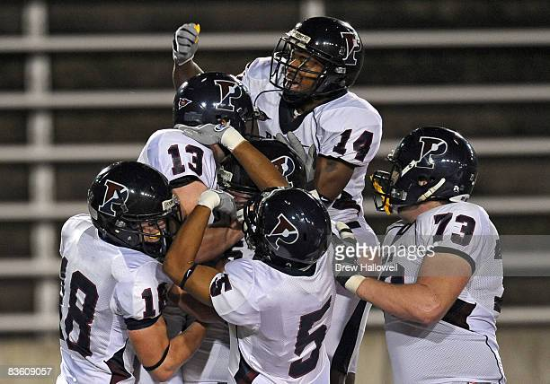 Wide receiver Tyler Fisher of the Pennsylvania Quakers and teammates thump on top of quarterback Keiffer Garton after he scored a touchdown during...