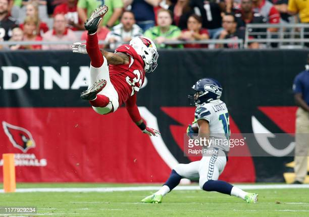 Wide receiver Tyler Lockett of the Seattle Seahawks catches a pass behind a leaping Budda Baker of the Arizona Cardinals during the first half of the...