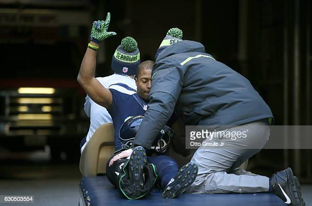 Wide receiver Tyler Lockett of the Seattle Seahawks gestures to the crowd as he leaves the game after getting injured in a play against the Arizona...