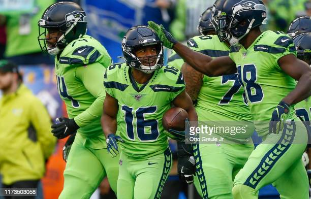 Wide receiver Tyler Lockett of the Seattle Seahawks is congratulated by teammates after scoring a touchdown in the first quarter against the Los...