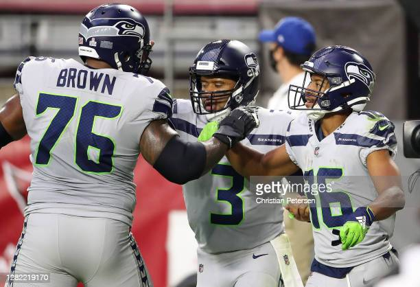 Wide receiver Tyler Lockett of the Seattle Seahawks is congratulated by offensive tackle Duane Brown and quarterback Russell Wilson after Lockett...