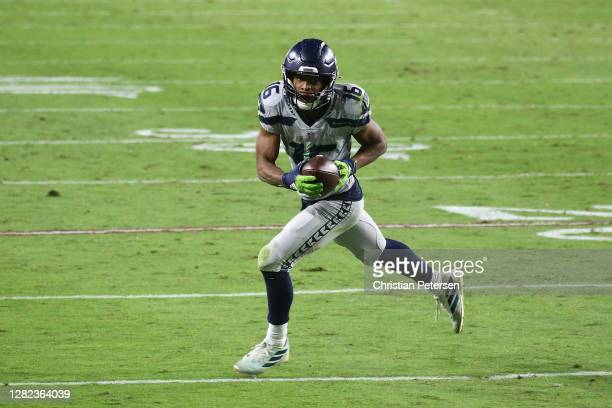 Wide receiver Tyler Lockett of the Seattle Seahawks runs with the football after a reception against the Arizona Cardinals during the NFL game at...