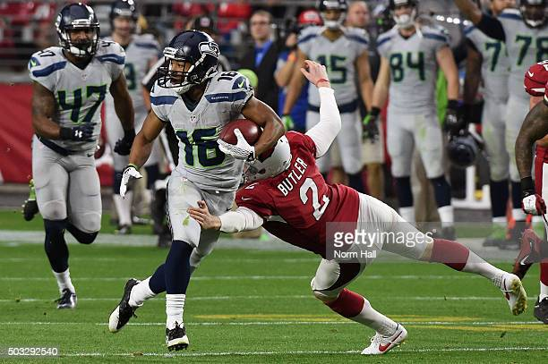 Wide receiver Tyler Lockett of the Seattle Seahawks runs with the football against punter Drew Butler of the Arizona Cardinals in the first half of...