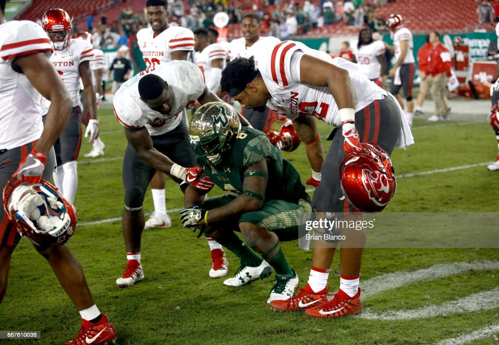 Wide receiver Tyre McCants #8 of the South Florida Bulls is comforted by running back Mulbah Car #34 of the Houston Cougars and tight end Romello Brooker #82 following the Bulls's 28-24 loss to the Cougars at an NCAA football game on October 28, 2017 at Raymond James Stadium in Tampa, Florida.