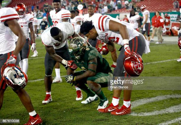Wide receiver Tyre McCants of the South Florida Bulls is comforted by running back Mulbah Car of the Houston Cougars and tight end Romello Brooker...