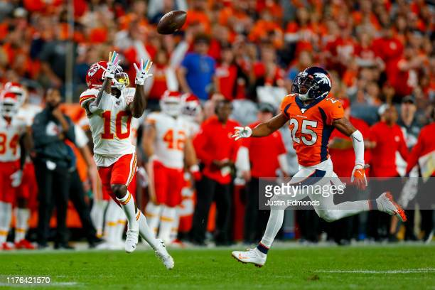 Wide receiver Tyreek Hill of the Kansas City Chiefs catches a pass against cornerback Chris Harris Jr. #25 of the Denver Broncos on his way to...