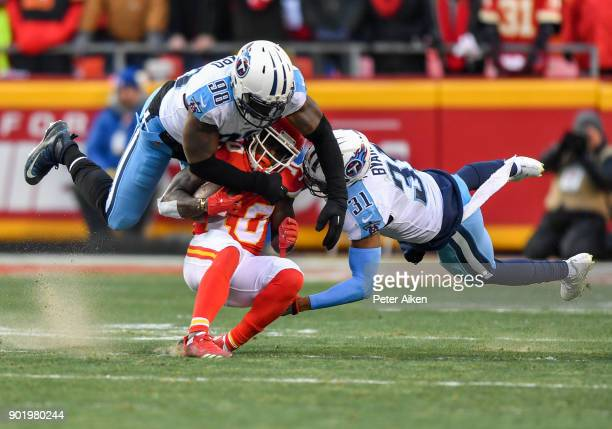 Wide receiver Tyreek Hill of the Kansas City Chiefs is tackled by outside linebacker Brian Orakpo and free safety Kevin Byard of the Tennessee Titans...