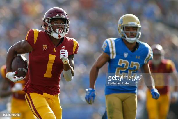 Wide receiver Velus Jones Jr #1 of the USC Trojans carries the ball toward the end zone as defensive back Nate Meadors of the UCLA Bruins follows...
