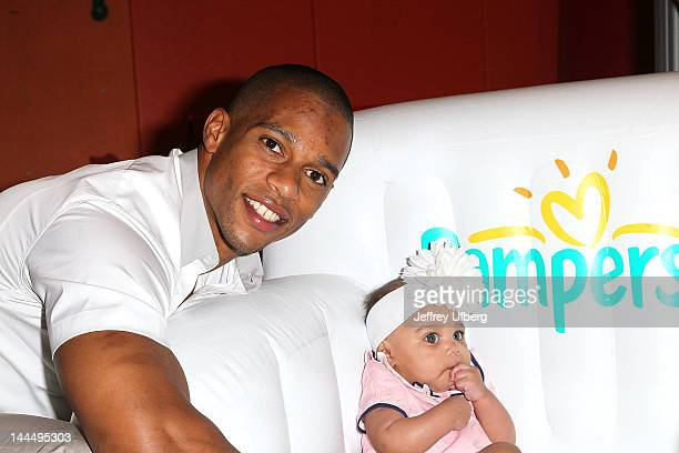 NFL wide receiver Victor Cruz and daughter Kennedy Cruz attend Pampers Spirit of Play Event In Celebration Of The London 2012 Olympics on May 14 2012...