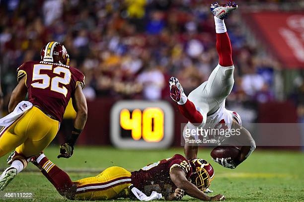 Wide receiver Victor Cruz of the New York Giants is hit by free safety Ryan Clark of the Washington Redskins in the second quarter at FedExField on...