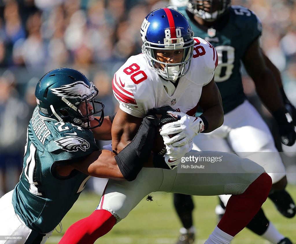 Wide receiver Victor Cruz #80 of the New York Giants is tackled by cornerback Bradley Fletcher #24 of the Philadelphia Eagles after making a catch during the first quarter of a game at Lincoln Financial Field on October 27, 2013 in Philadelphia, Pennsylvania. Vick recovered the fumble.
