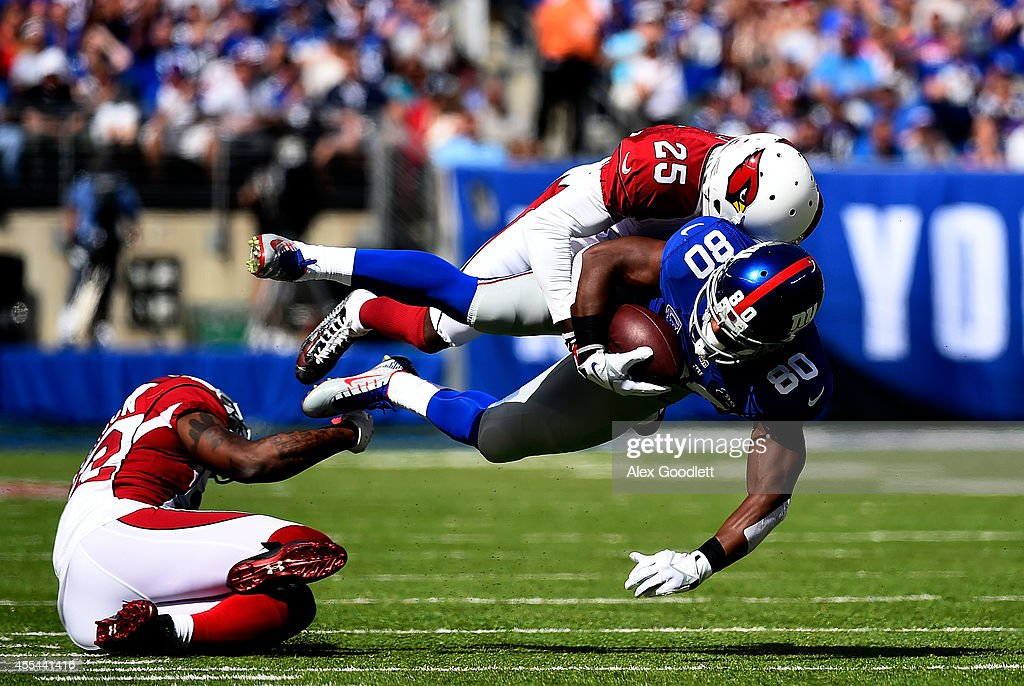 Wide receiver Victor Cruz #80 of the New York Giants is tackled by cornerback Jerraud Powers #25 of the Arizona Cardinals during a game at MetLife Stadium on September 14, 2014 in East Rutherford, New Jersey.