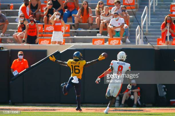 Wide receiver Winston Wright Jr. #16 of the West Virginia Mountaineers scores a 70-yard touchdown against cornerback Rodarius Williams of the...