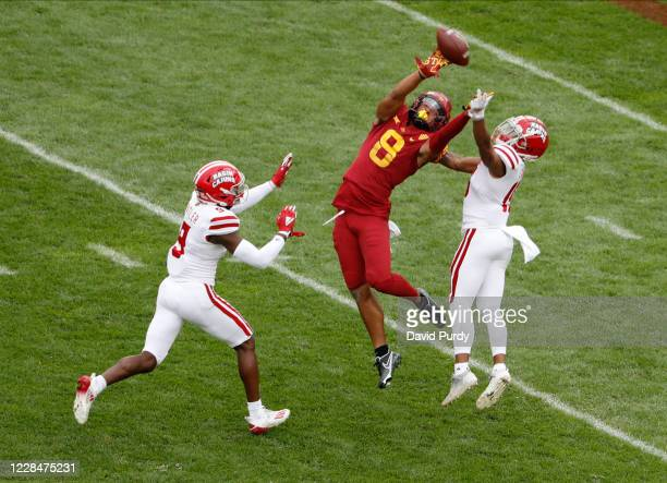 Wide receiver Xavier Hutchinson of the Iowa State Cyclones tries to pull in a pass as safety Percy Butler and cornerback Eric Garror of the...