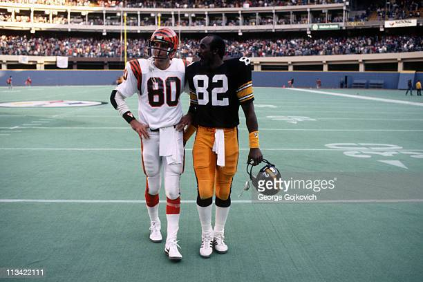 Wide receivers Cris Collinsworth of the Cincinnati Bengals and John Stallworth of the Pittsburgh Steelers walk off the field following their game at...