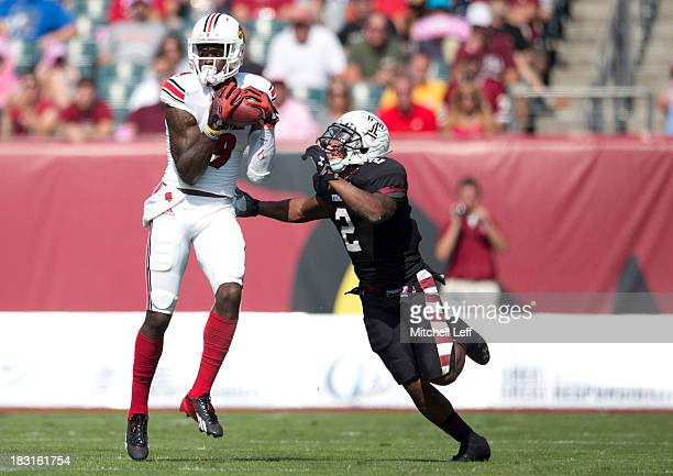 Wide reciever Devante Parker of the Louisville Cardinals catches a pass against cornerback Anthony Robey of the Temple Owls on October 5 2013 at...
