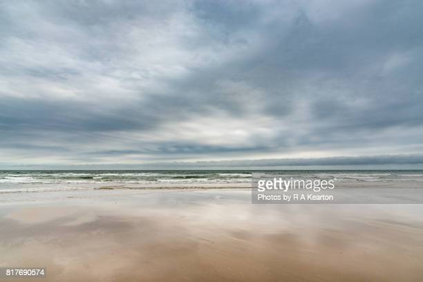wide sandy beach below moody sky - nuvoloso foto e immagini stock