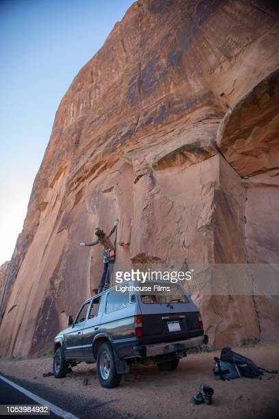 Wide shot. Adventurous man in rock climbing gear stands atop a sports utility vehicle with hands in the air, looks in awe of giant canyon rockface in preparation for a climb in Moab, Utah.