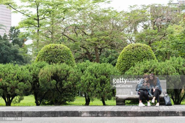 Wide shot female friends using phone looking at social media sitting on a park bench