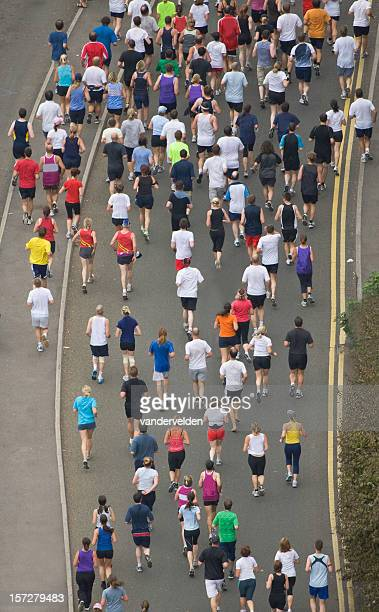 a wide shot from above of people running in a competition - marathon stock pictures, royalty-free photos & images