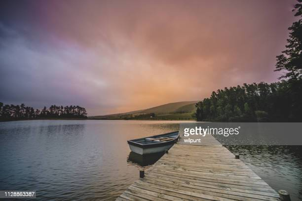 wide shot of a moored rowboat and jetty serenity scene at dawn - moored stock pictures, royalty-free photos & images