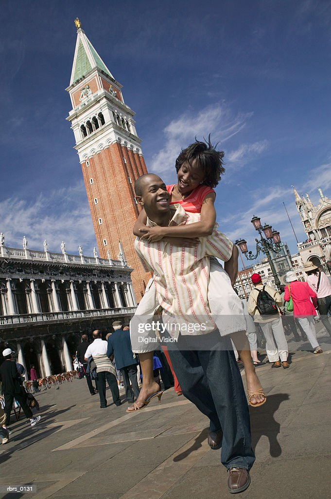 wide shot of a young adult couple as the man carries the woman while sightseeing in Venice : Foto de stock