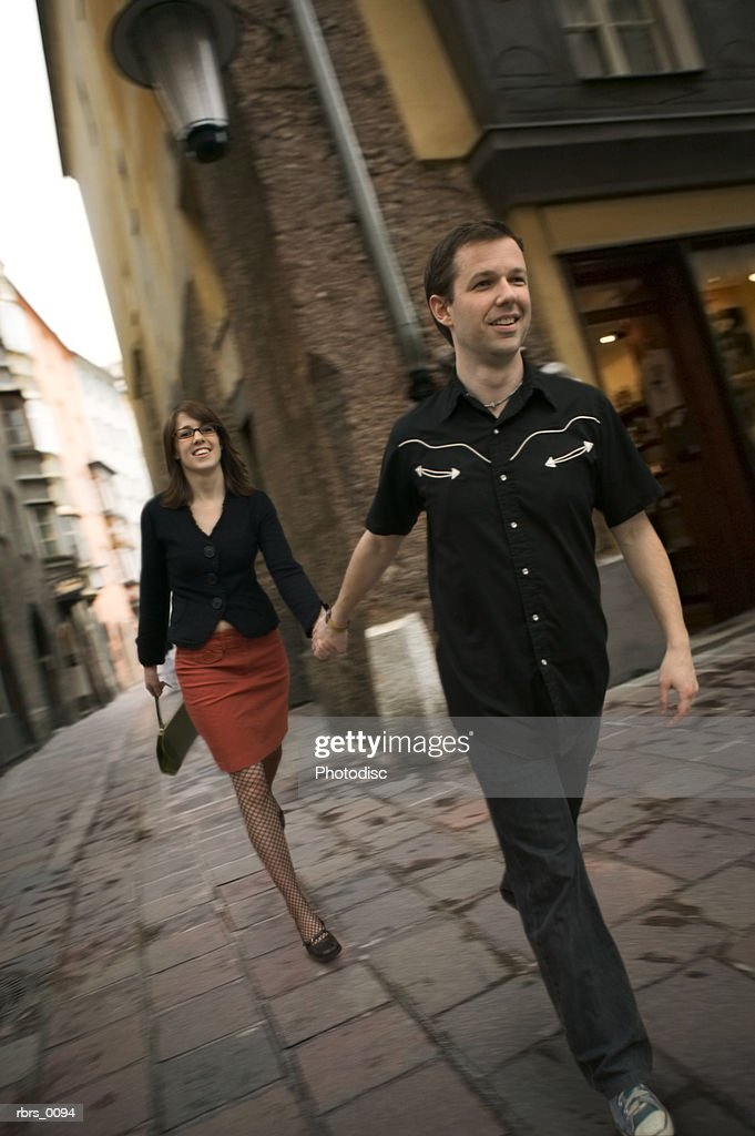 wide shot of a young adult couple as the man leads the woman down a cobblestone road : Foto de stock