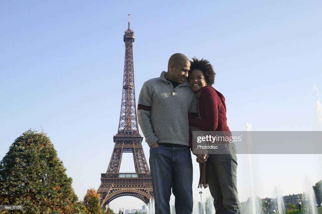 wide shot of a young adult couple as they cuddle together at the eiffel tower in paris : Foto de stock