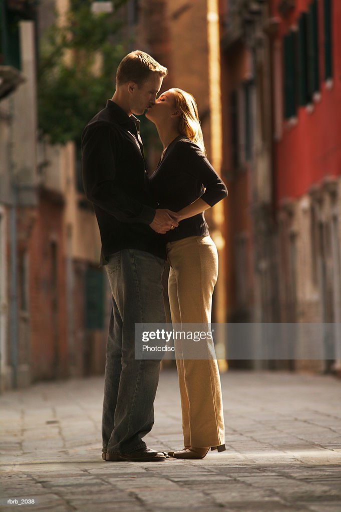 wide shot of a young adult couple as they hug and kiss on an old cobblestone road : Stockfoto