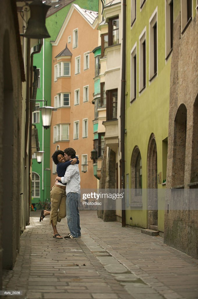 wide shot of a young adult couple as they hug on an old cobblestone street : Stockfoto
