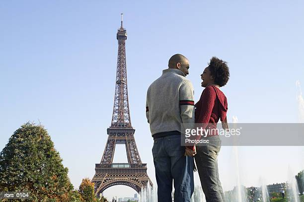 wide shot of a young adult couple as they laugh together at the eiffel tower in paris