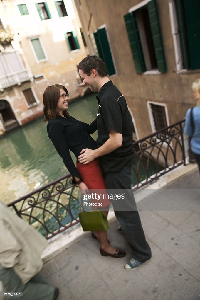 wide shot of a young adult couple as they look into each others eyes on a bridge : Stockfoto