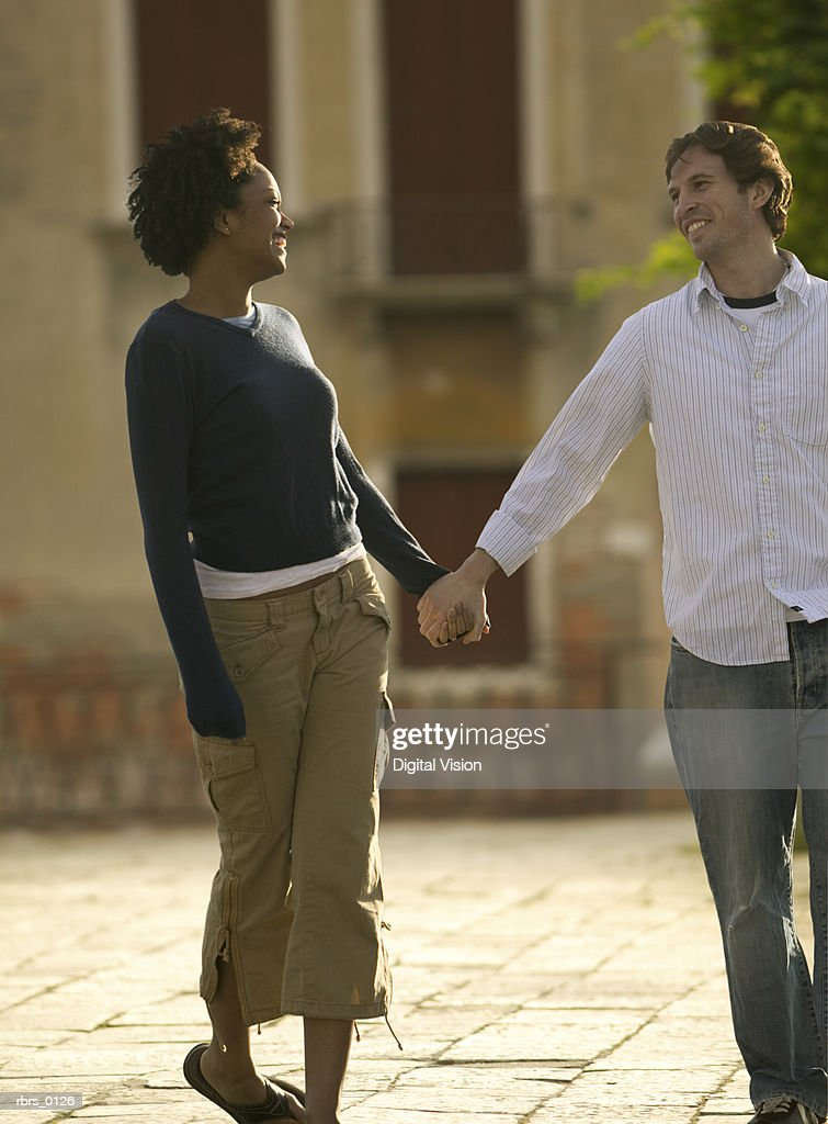 wide shot of a young adult couple as they stroll down the road hand in hand : Foto de stock
