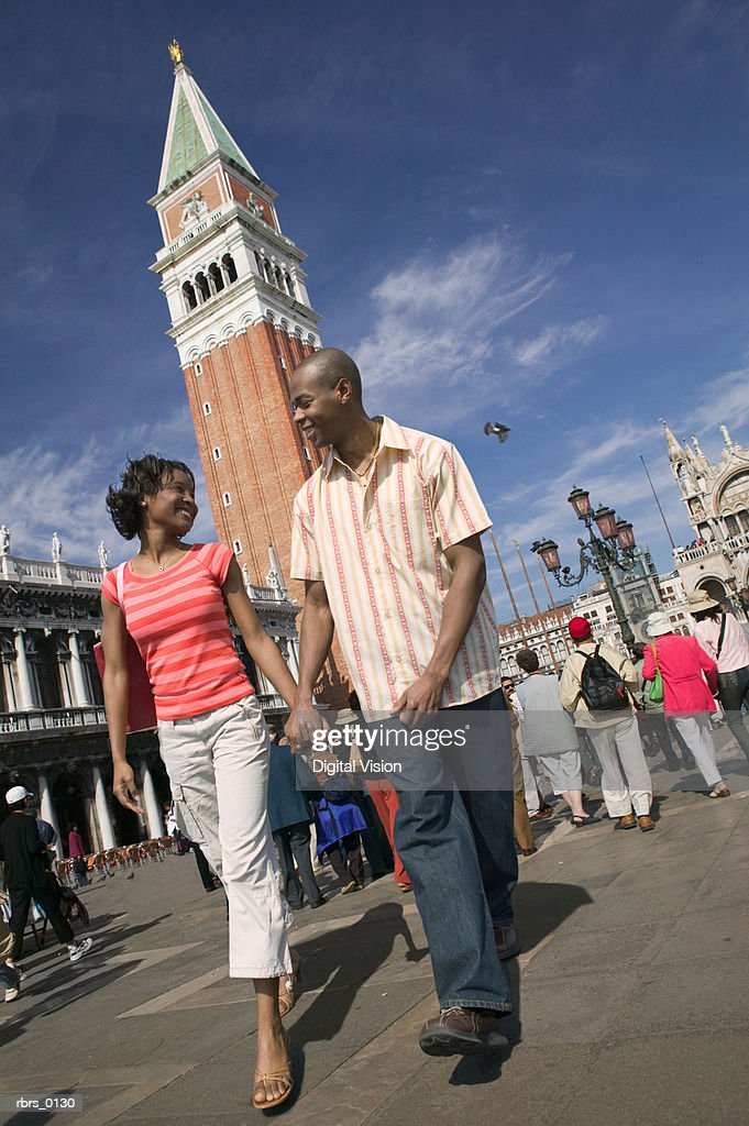 wide shot of a young adult couple as they walk hand in hand while vacationing in Venice : Foto de stock